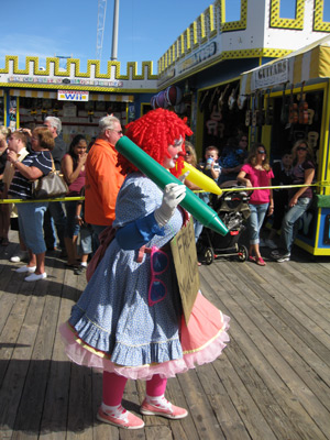 a single clown walking along the boardwalk