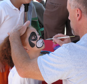 a child having her face painted with a mouse design